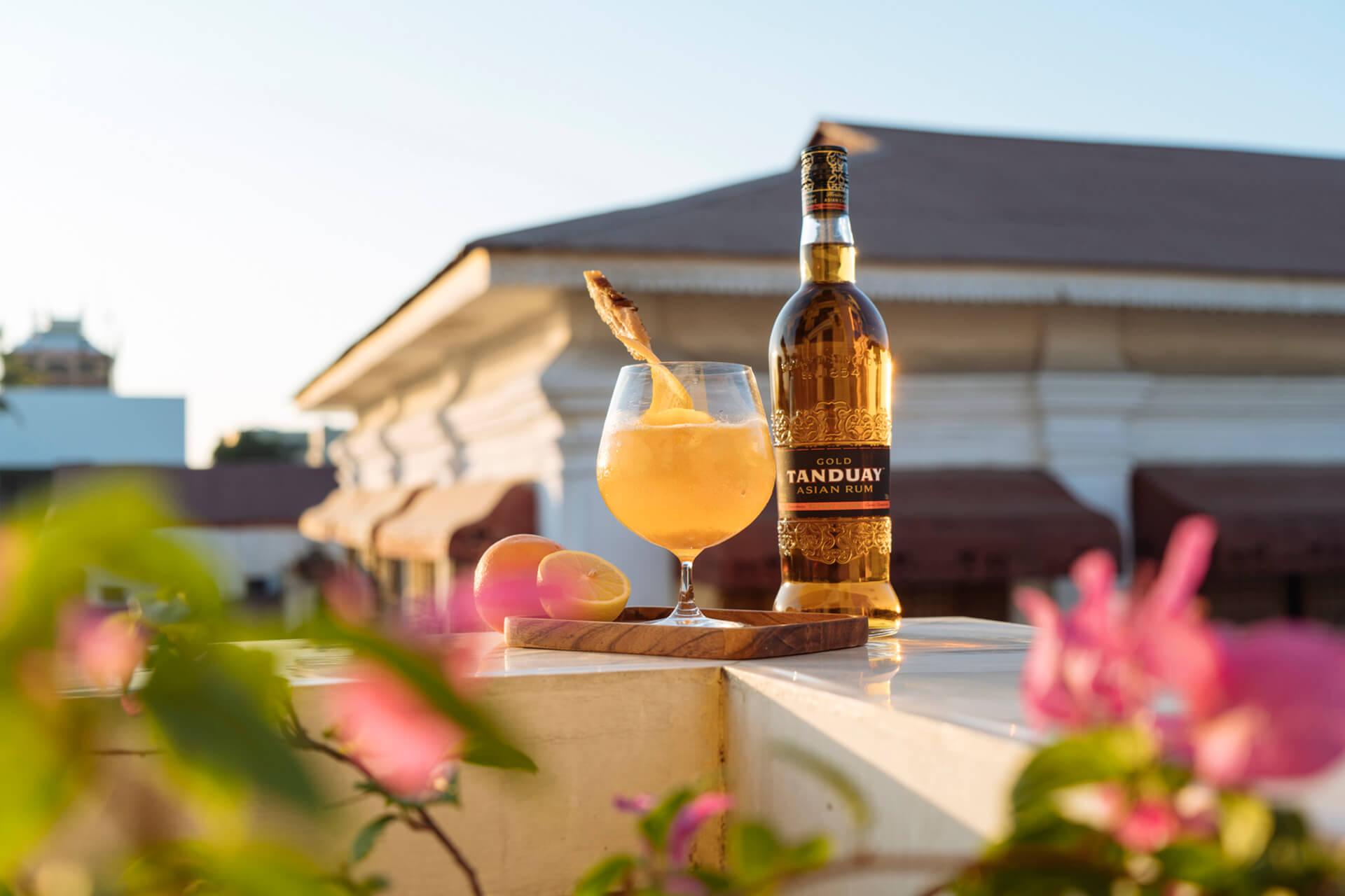 Tandauy Asian Rum with pineapple garnish on a balcony overlooking Vigan's Kalye Crisologo.