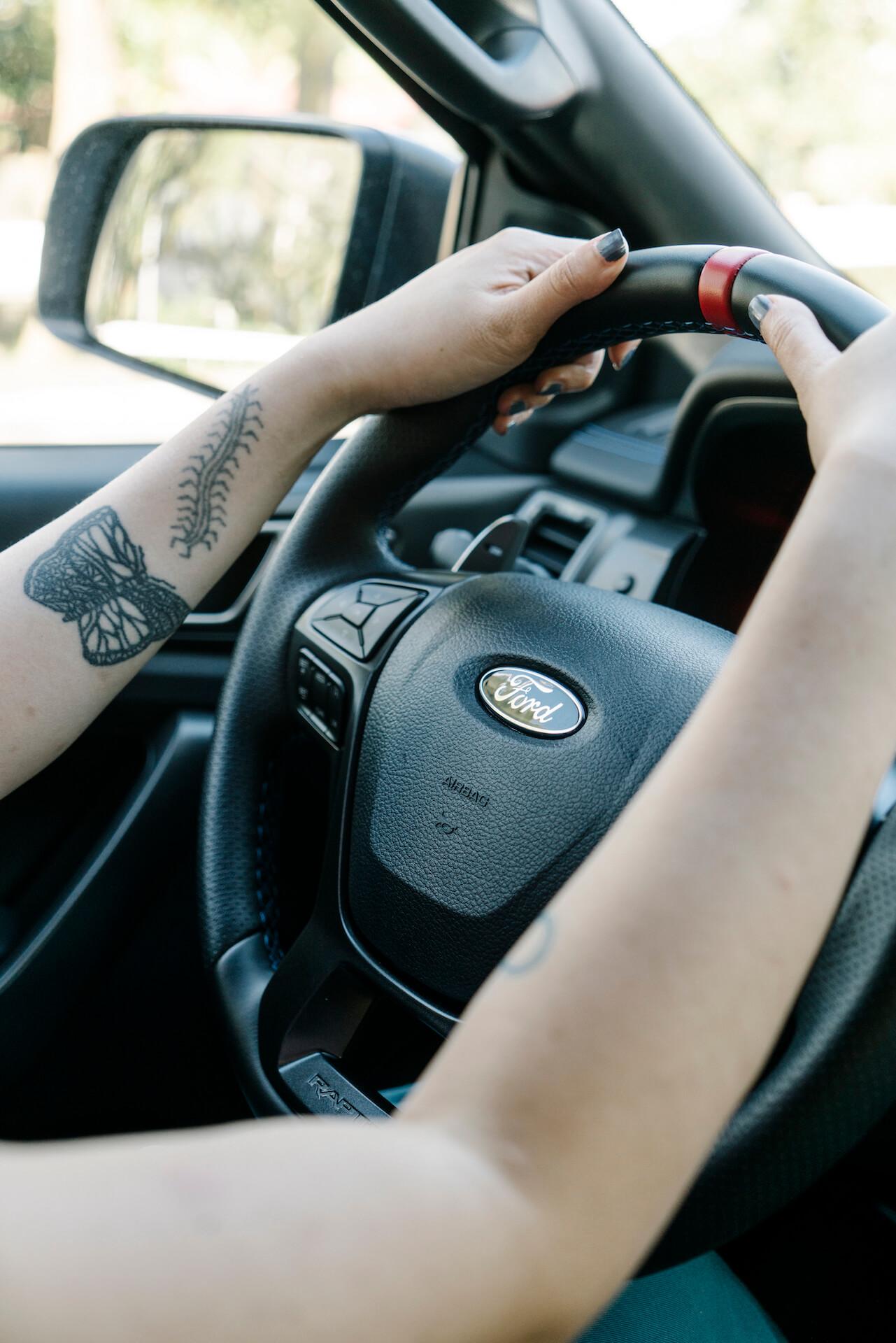 A woman with tattoos grips the steering wheel of a Ford Raptor