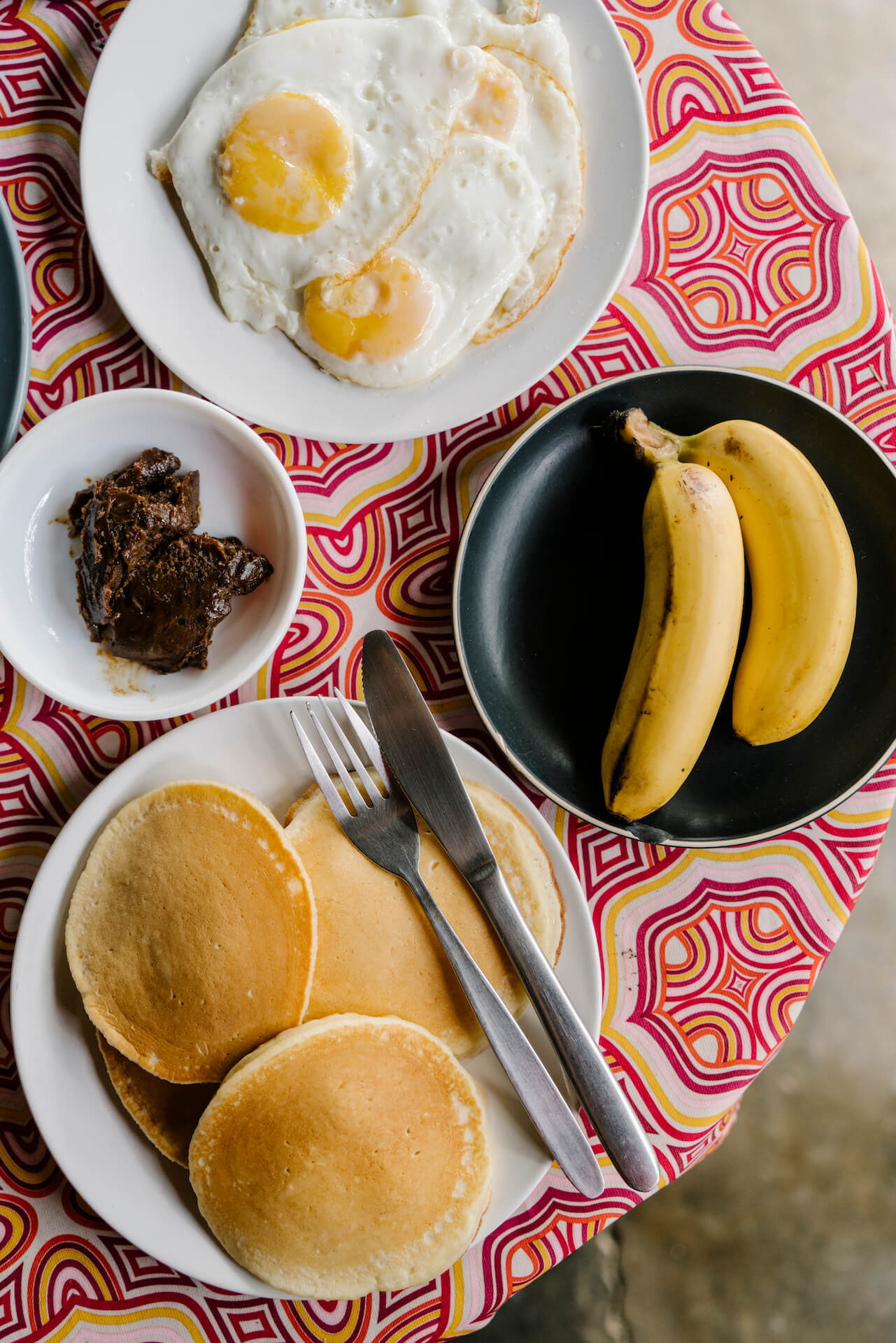 A breakfast spread of pancakes, eggs, and bananas