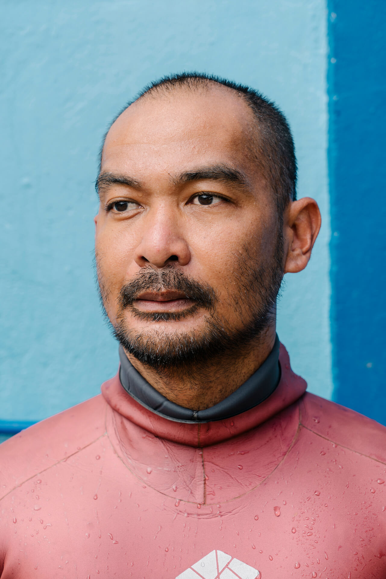 Carlo Navarro in a wetsuit poses outside of the ManuMano freedive house
