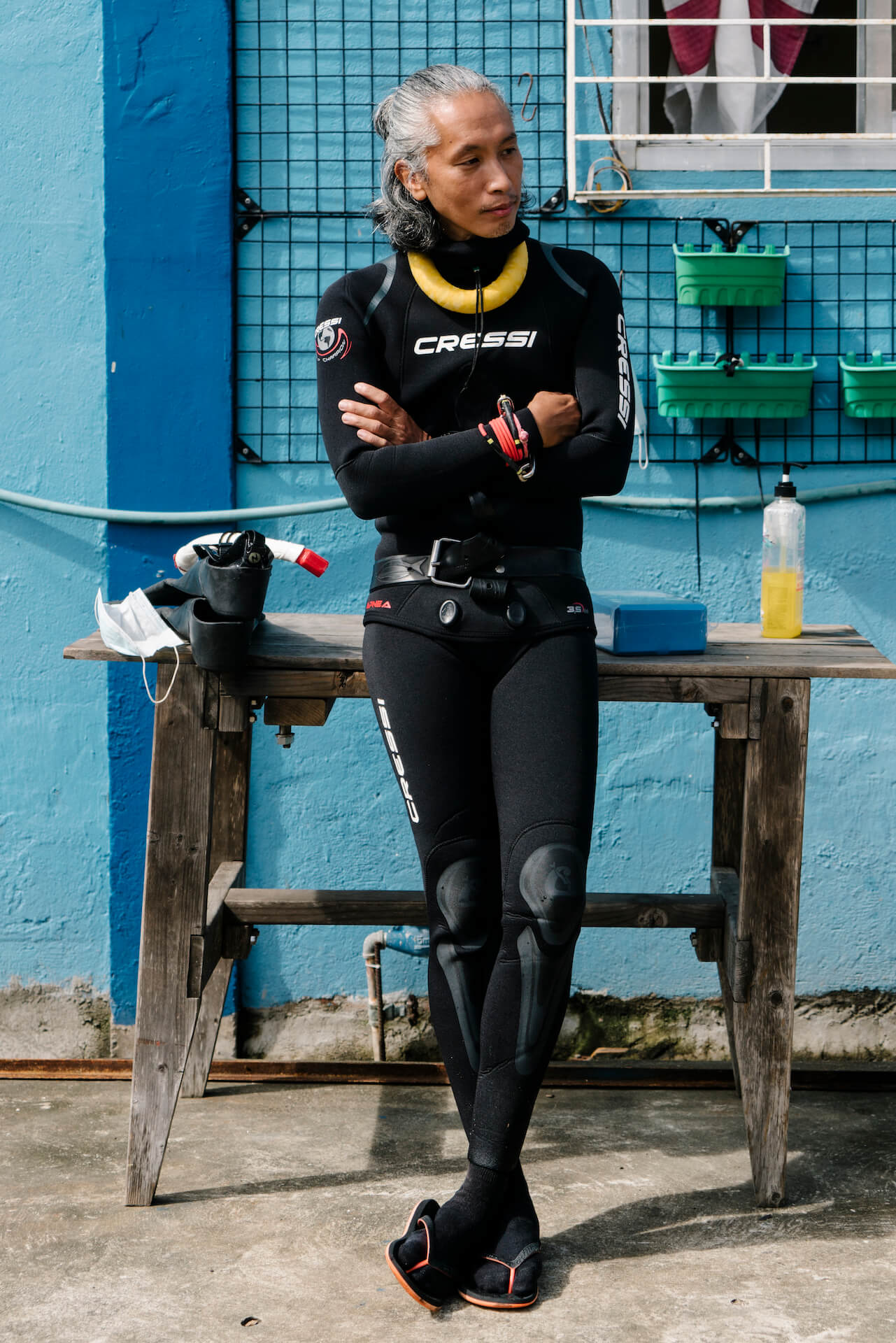 A male diver wearing a wetsuit waits outside the ManuMano freedive house