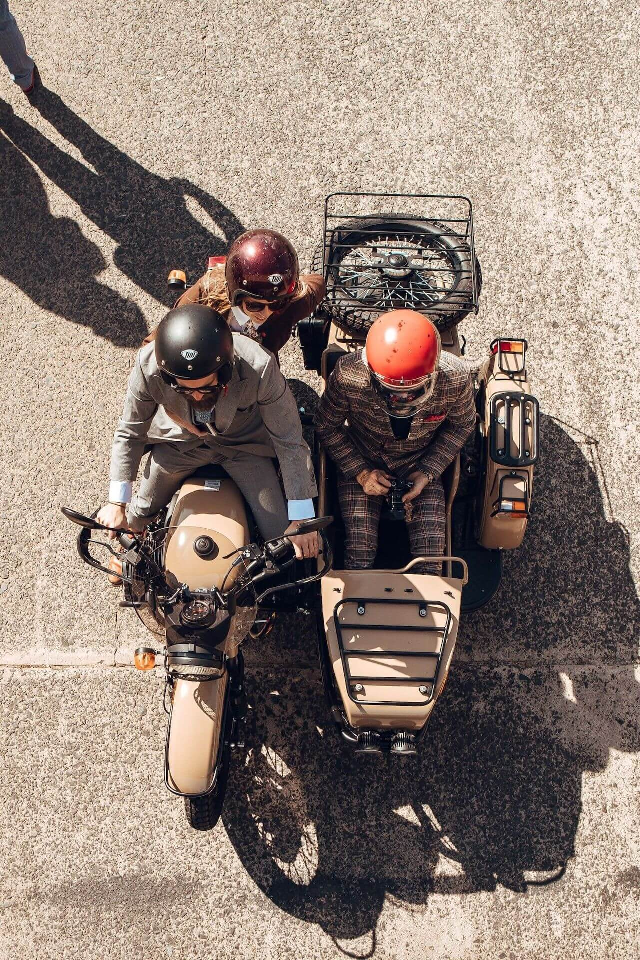 Three dressed in suits riding a vintage style motorbike with a sidecar