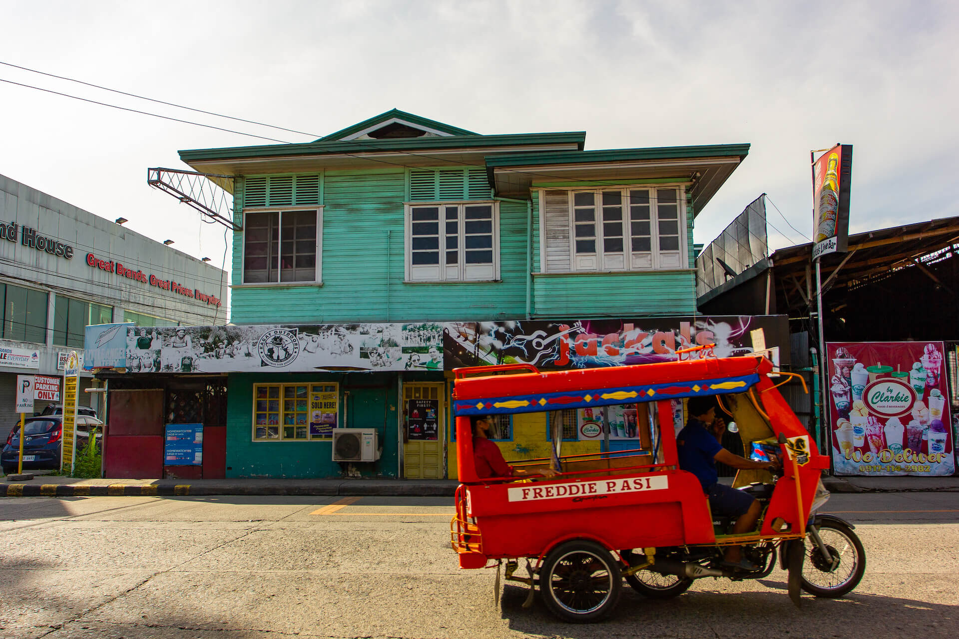 A motorela passing through Corrales St., which is lined with homegrown restos and bars