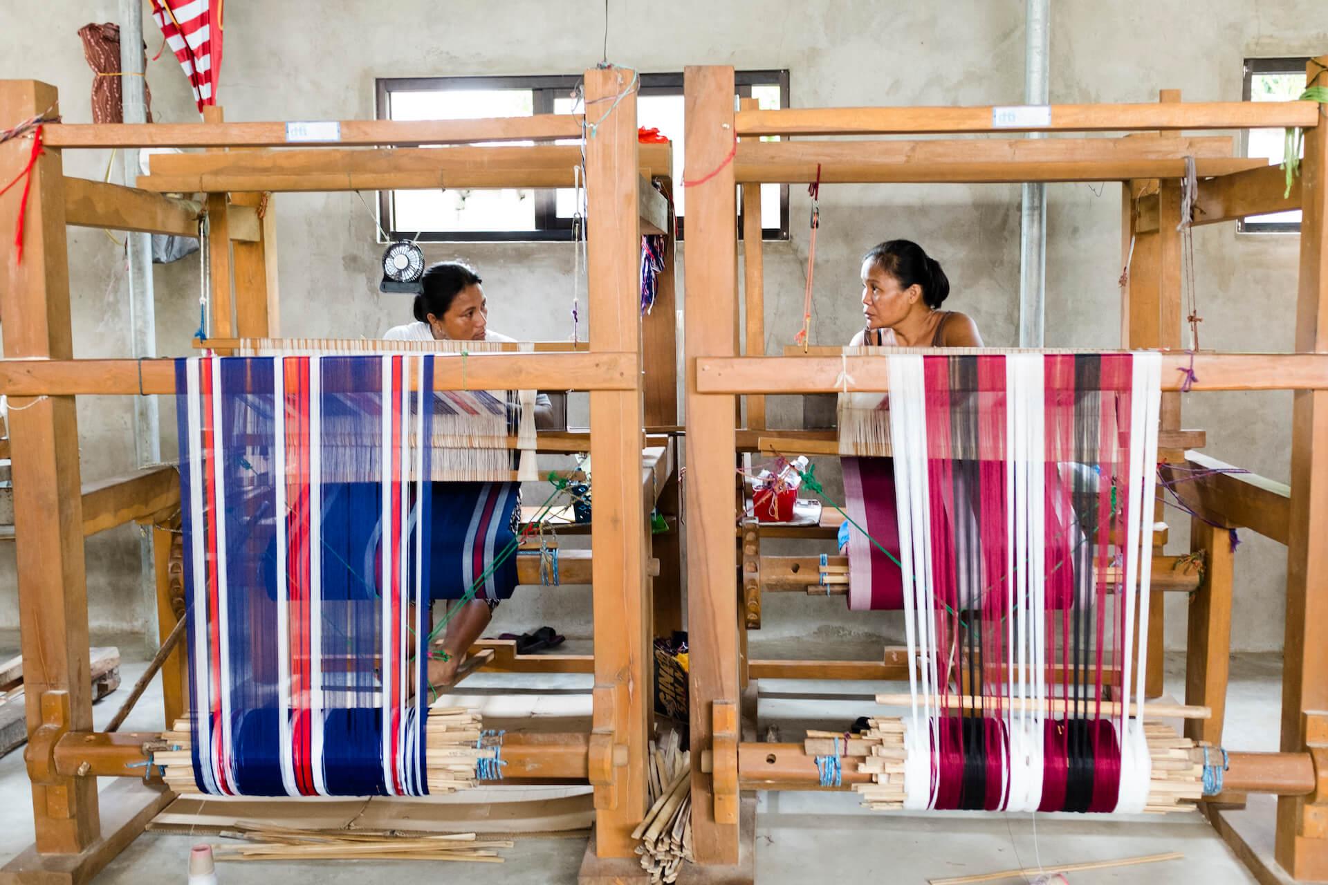 ANTHILL weavers sit behind upright floor looms