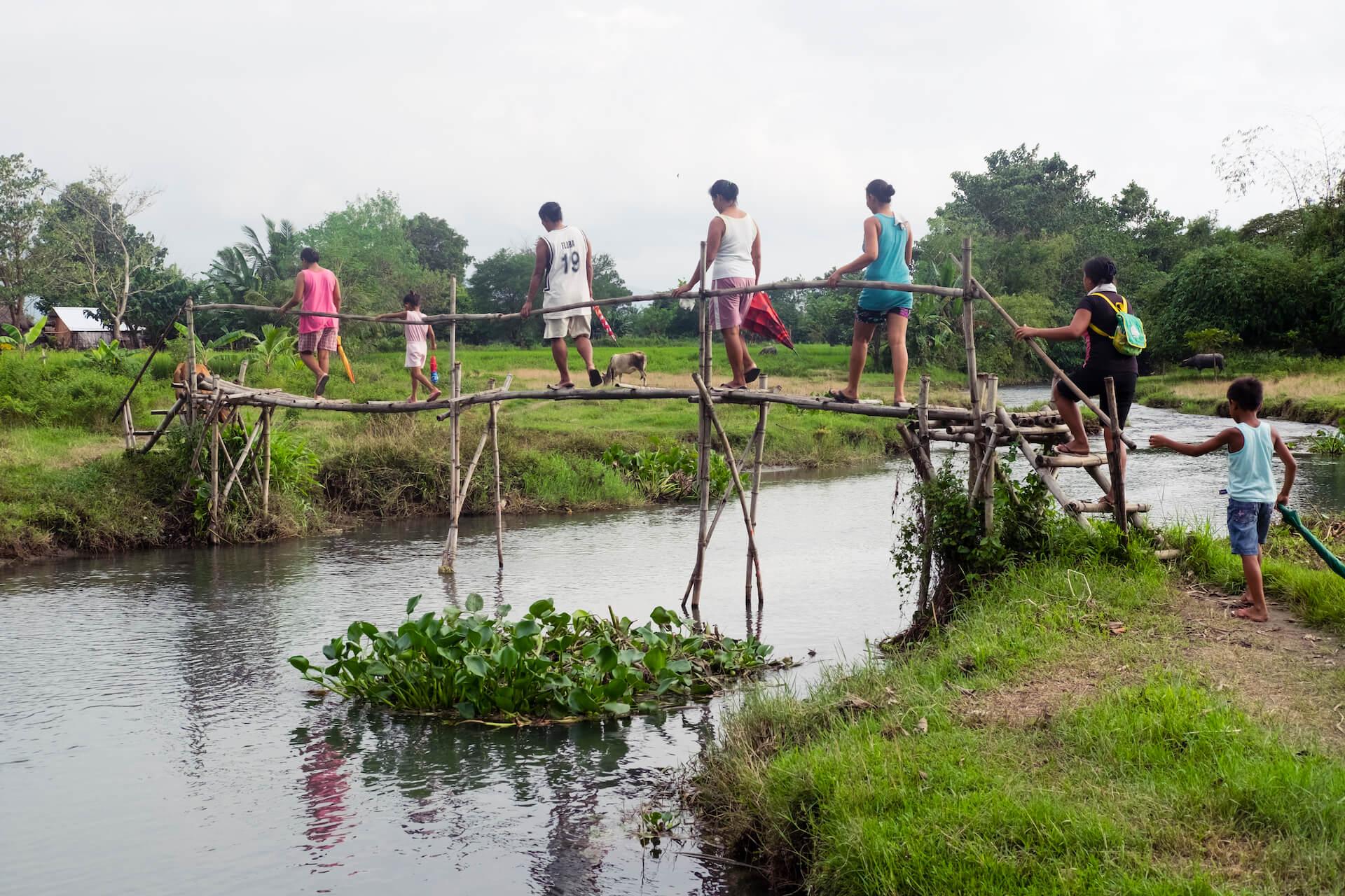 The women cross a bamboo bridge in Brgy. Bulbulala, La Paz, to visit the home of a fellow weaver