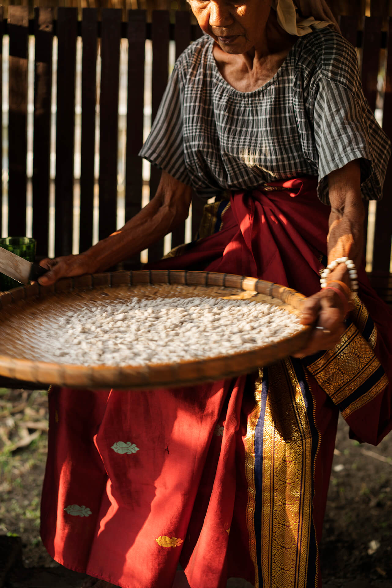 A woman sorts grains on a bilao in Maguindanao, photo by Sonny Thakur