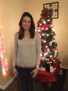Nicole posing in front of the Christmas Tree at the City Mission Women with Children Center