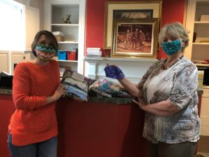 Two City Mission Staffers show-off their new protective cloth face-masks