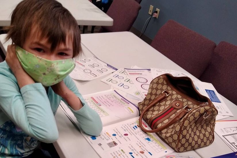 A city mission child resident, donning a protective mask, gets home schooled