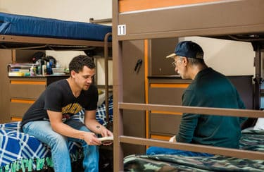 Two male residents sit on bunks opposite each other having a discussion