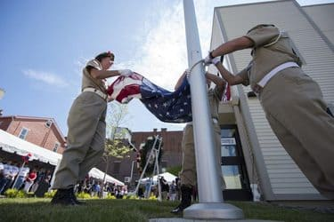 Two members of the American Legion unfold the flag prior to raising it at the opening of the Crabtree-Kovacicek Veterans House