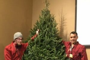 Two City Mission residents decorating Christmas tree