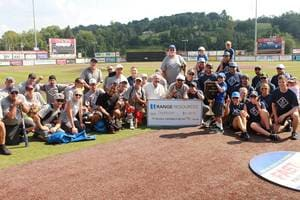 Participant softball players at City Mission's 'Hits for the Homeless' event - here Dean Gartland receives a check from Range Resources as the sponsor of the game