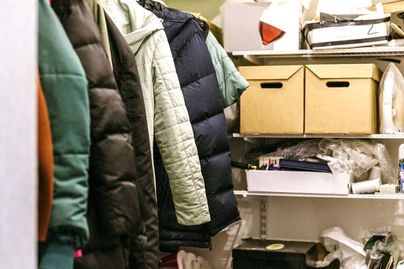 a cluttered up closet full of coats, clothes, tools and other personal effects