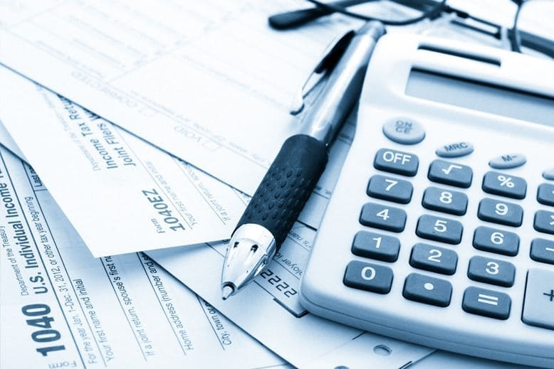 calculator, pen and paper for working on taxes