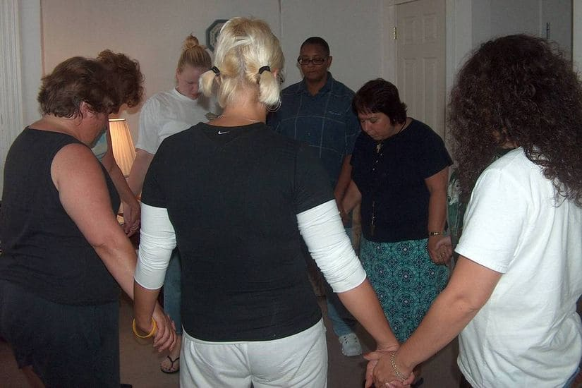 women engaging in group prayer