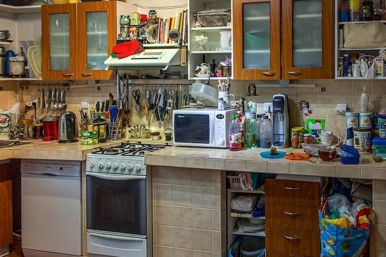 a cluttered kitchen with various arrangements of junk all over the counters
