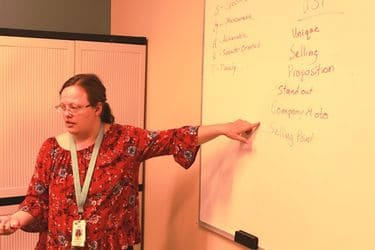 Brianna Kadlecik stands at a white-board providing instruction during a classroom session