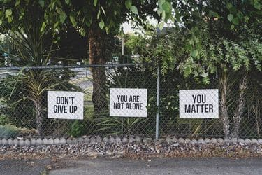 3 signs on a fence: don't give up; you're not alone; you matter.