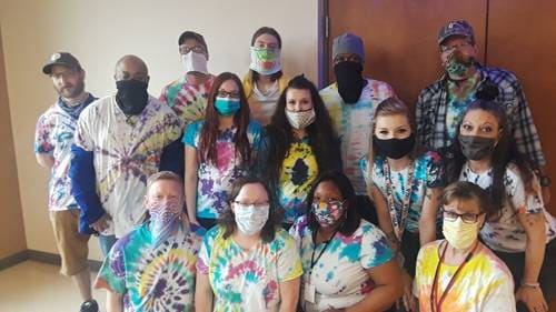 staff and residents gather for photo op with masks