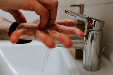 pair of hands being washed in sink