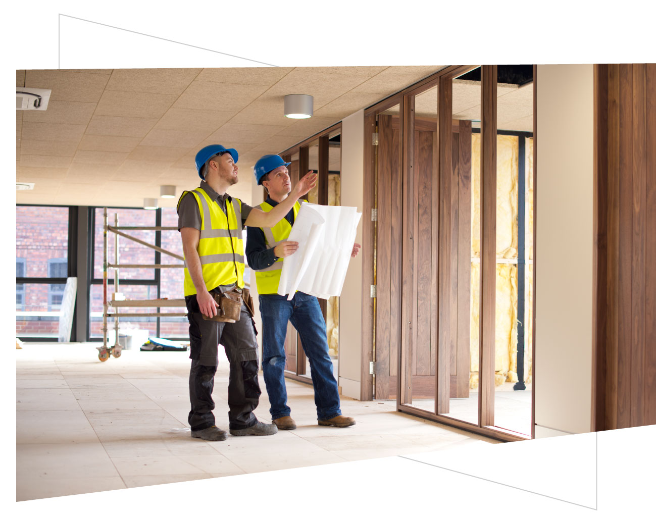two construction workers looking at blueprint in an under construction office