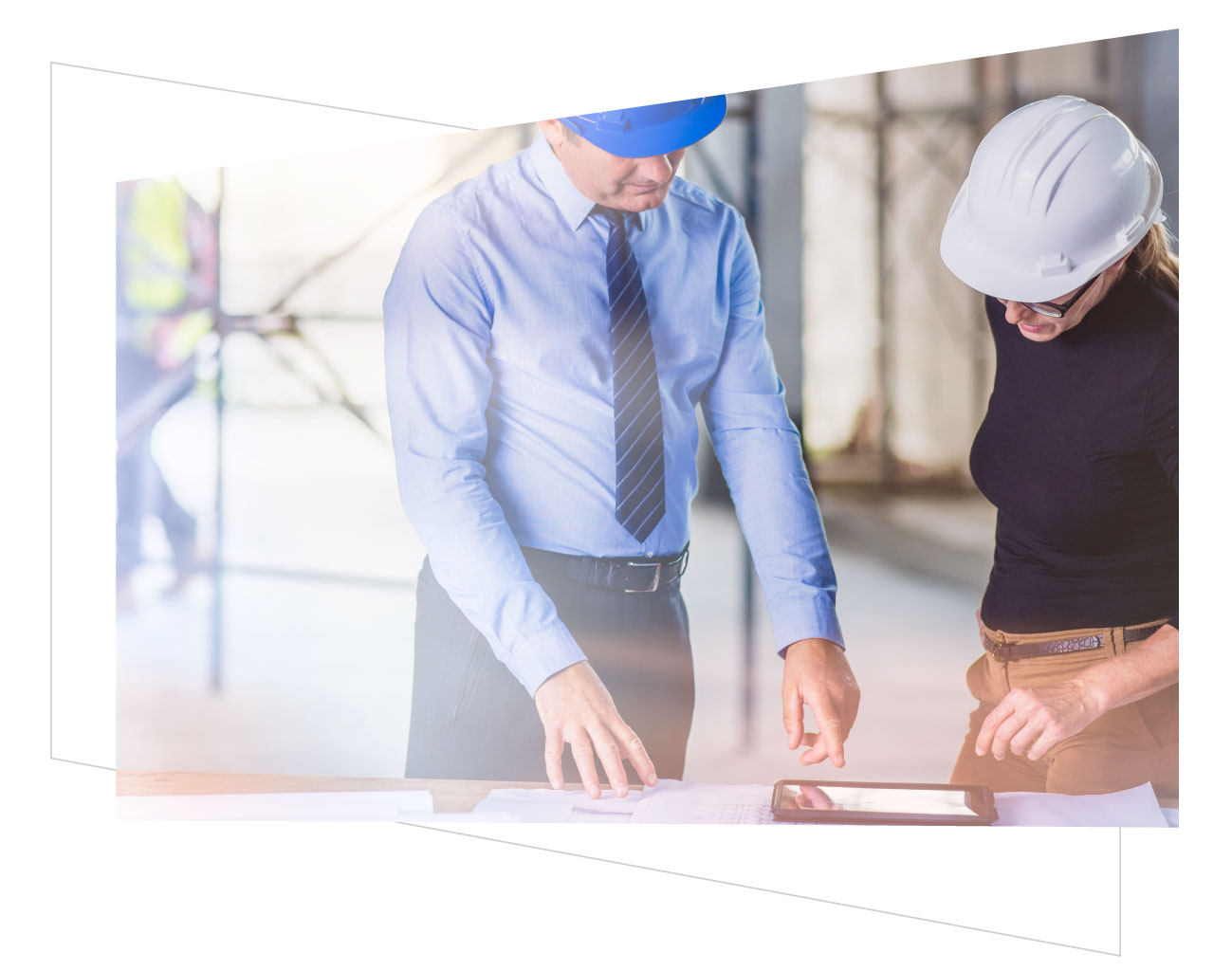 two real estate managers with hard hats looking at blueprints on ipad