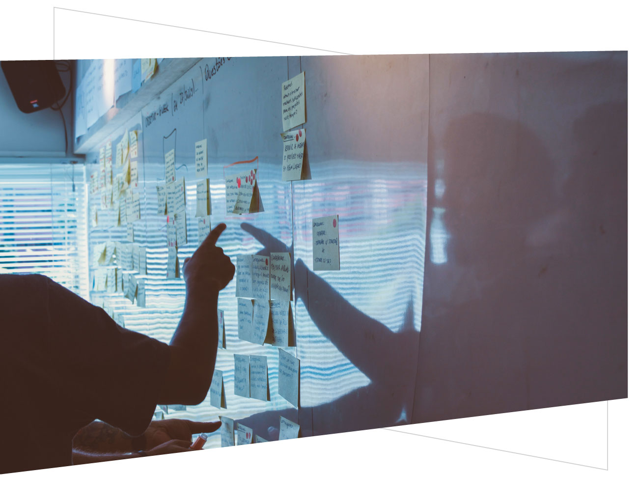 brainstorming session with many post it notes on a white board and man pointing at one