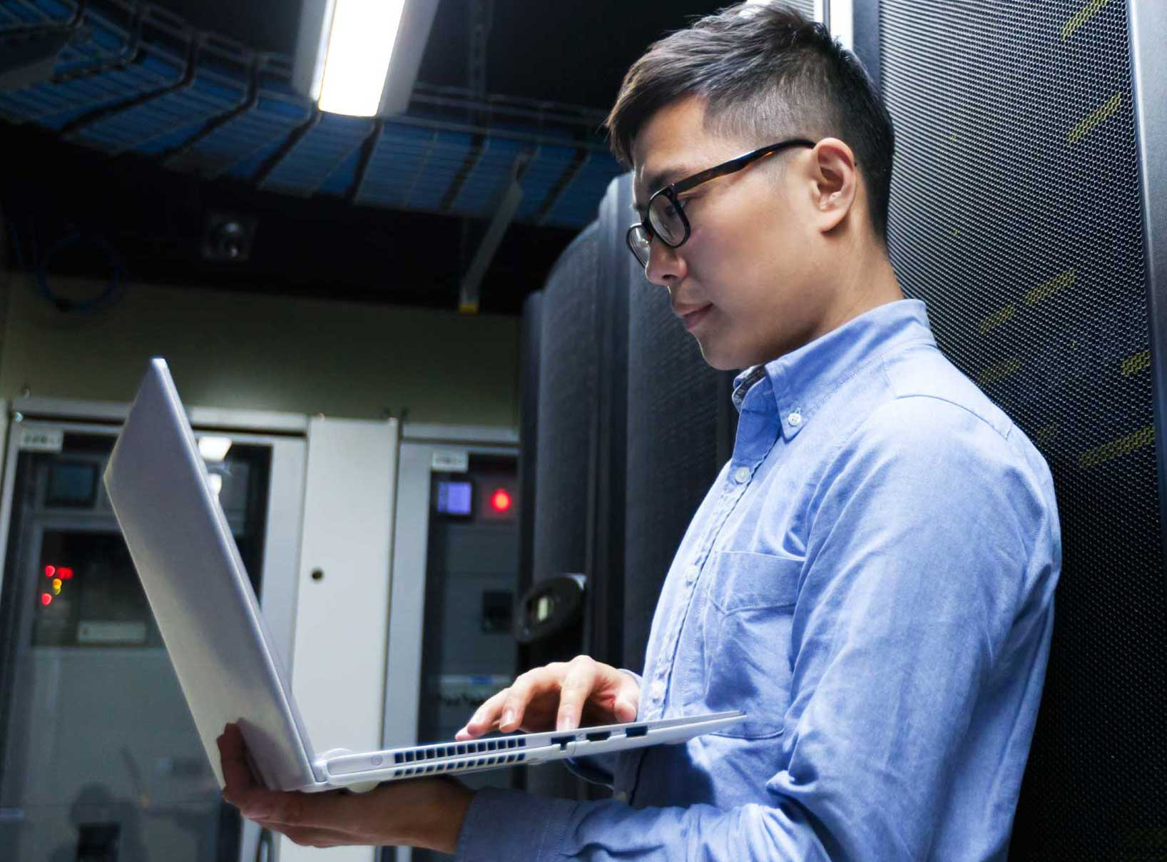 photo of man holding laptop standing in server room