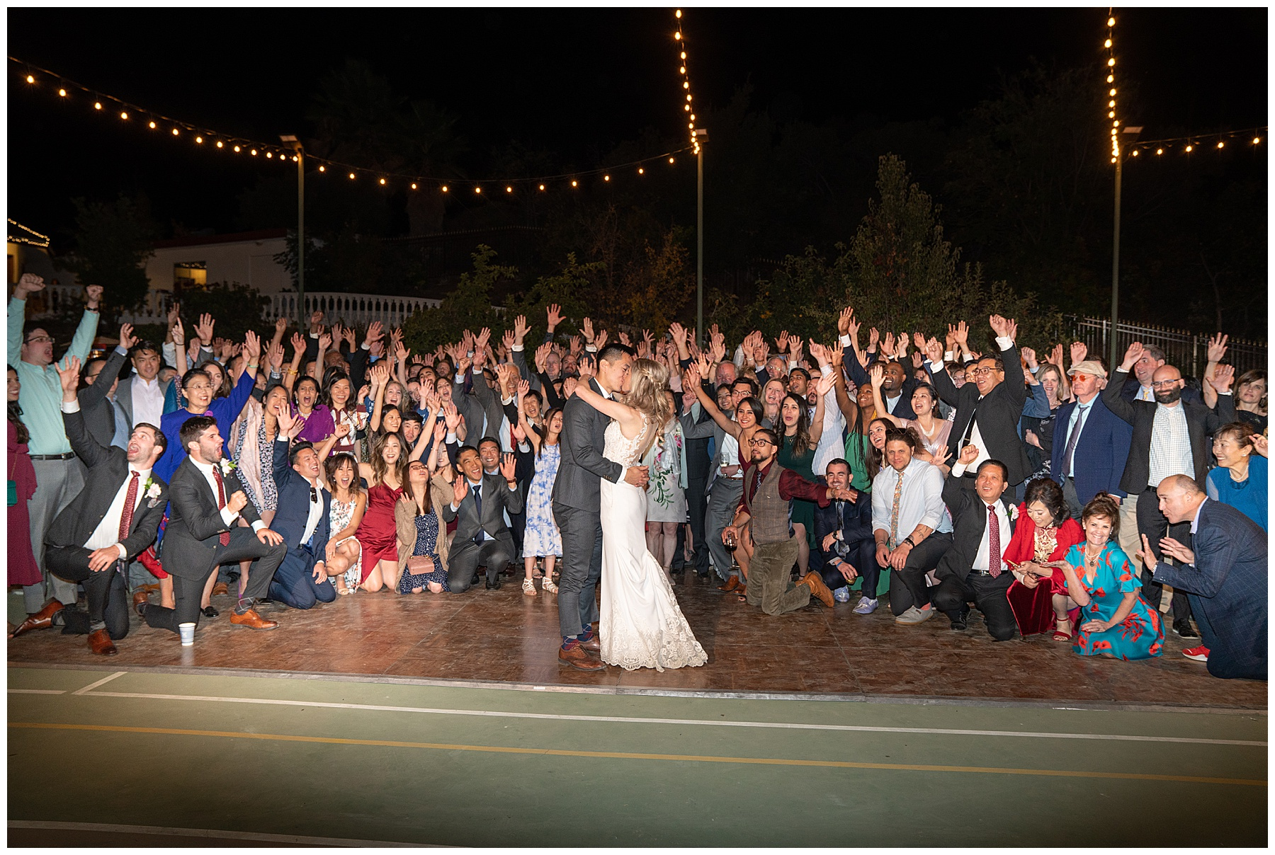 group photo of all wedding guests on dance floor