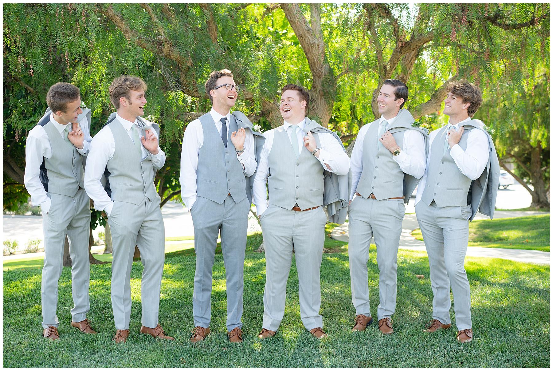 groomsmen with coats over their shoulders