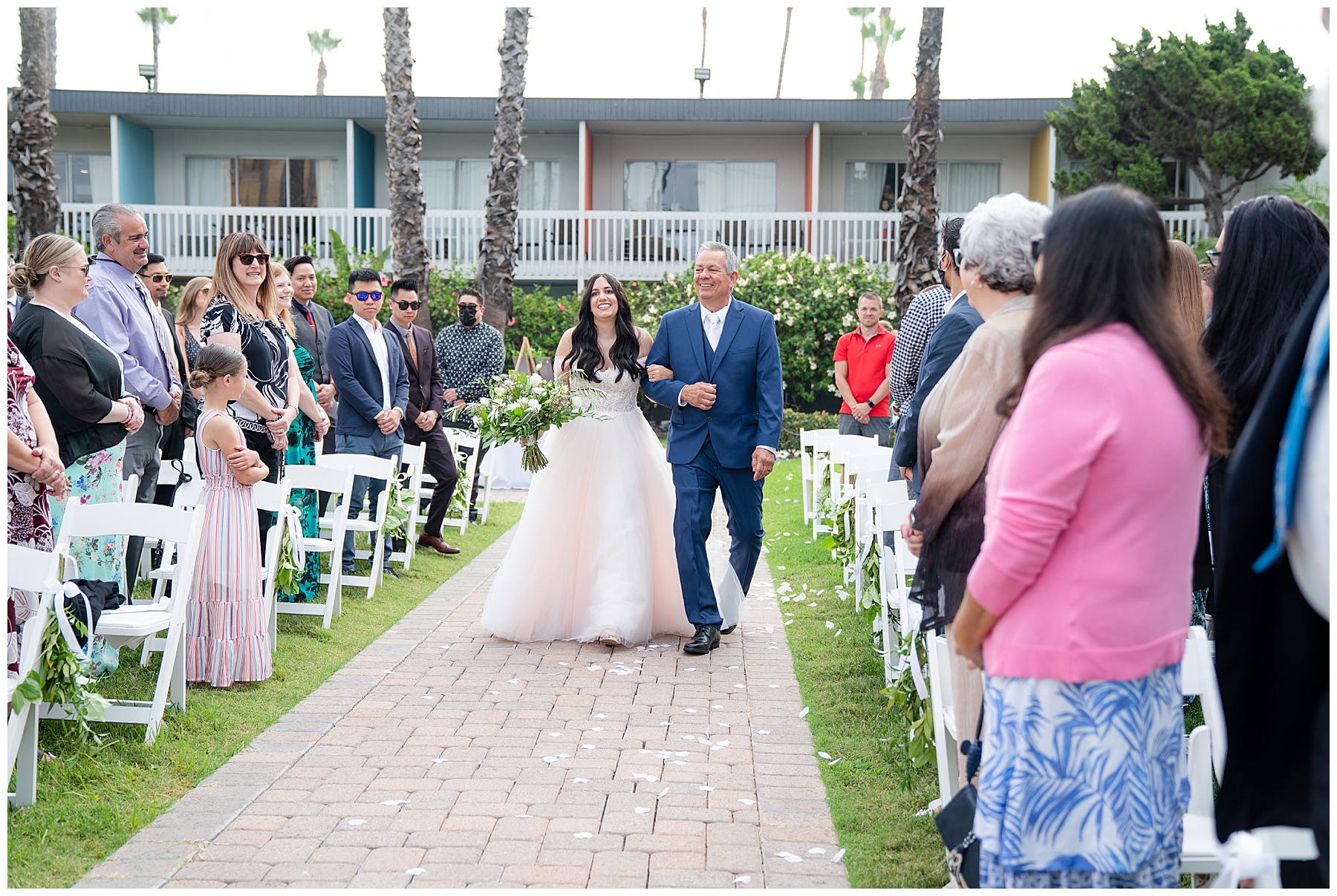 bride walking down the aisle with dad in blue