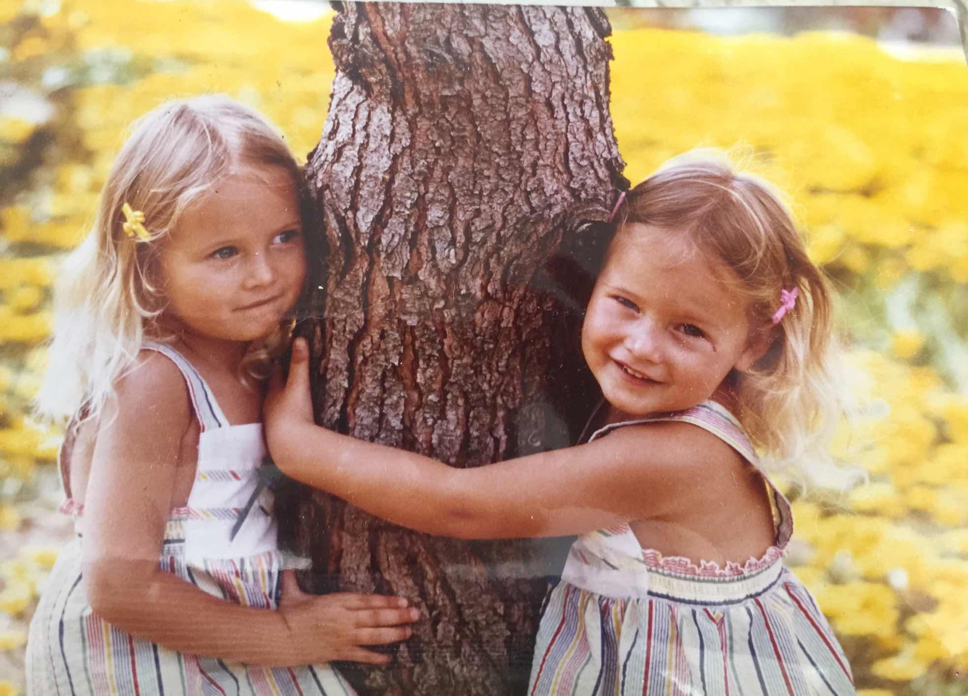 identical twin girls hugging a tree