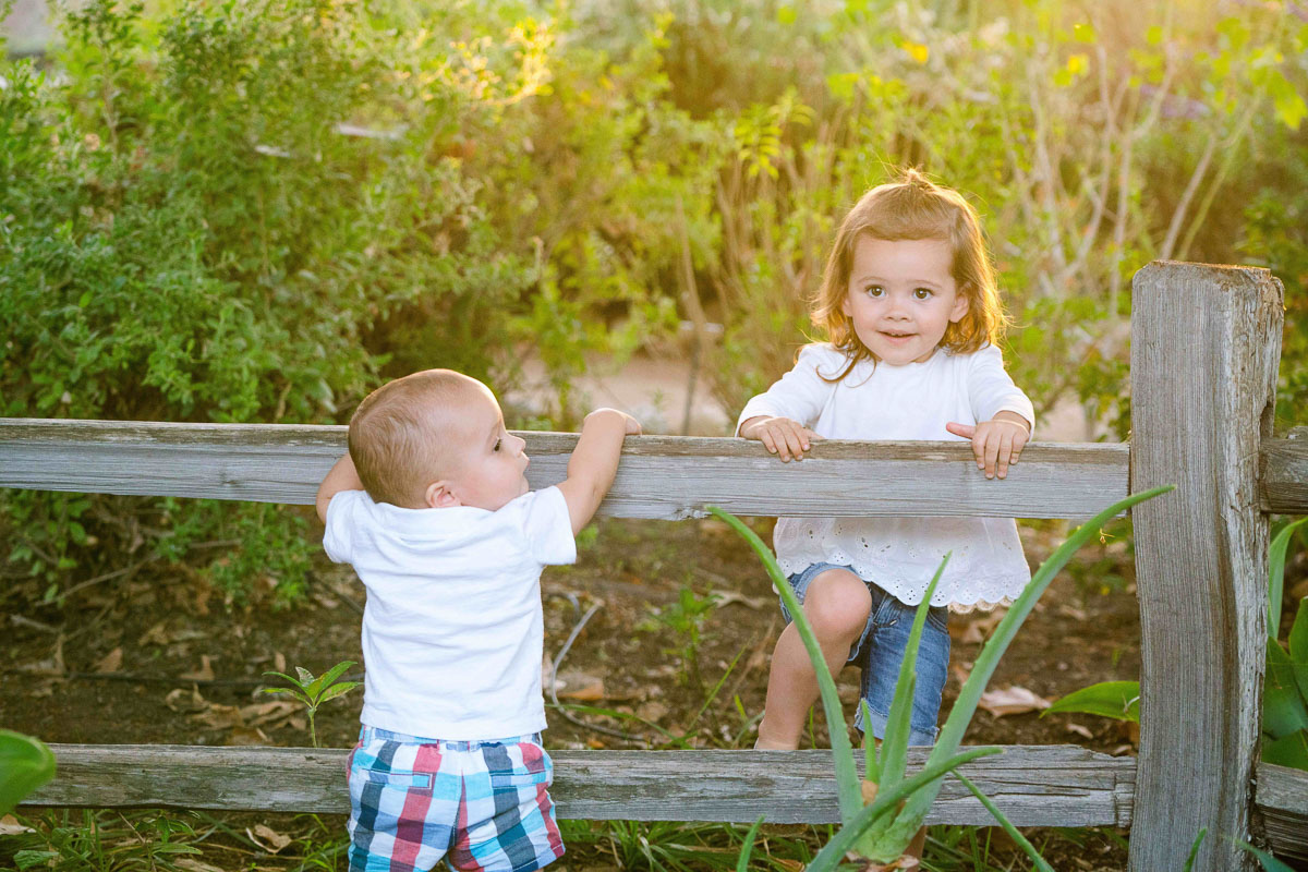 little boy and girl playing on a fence