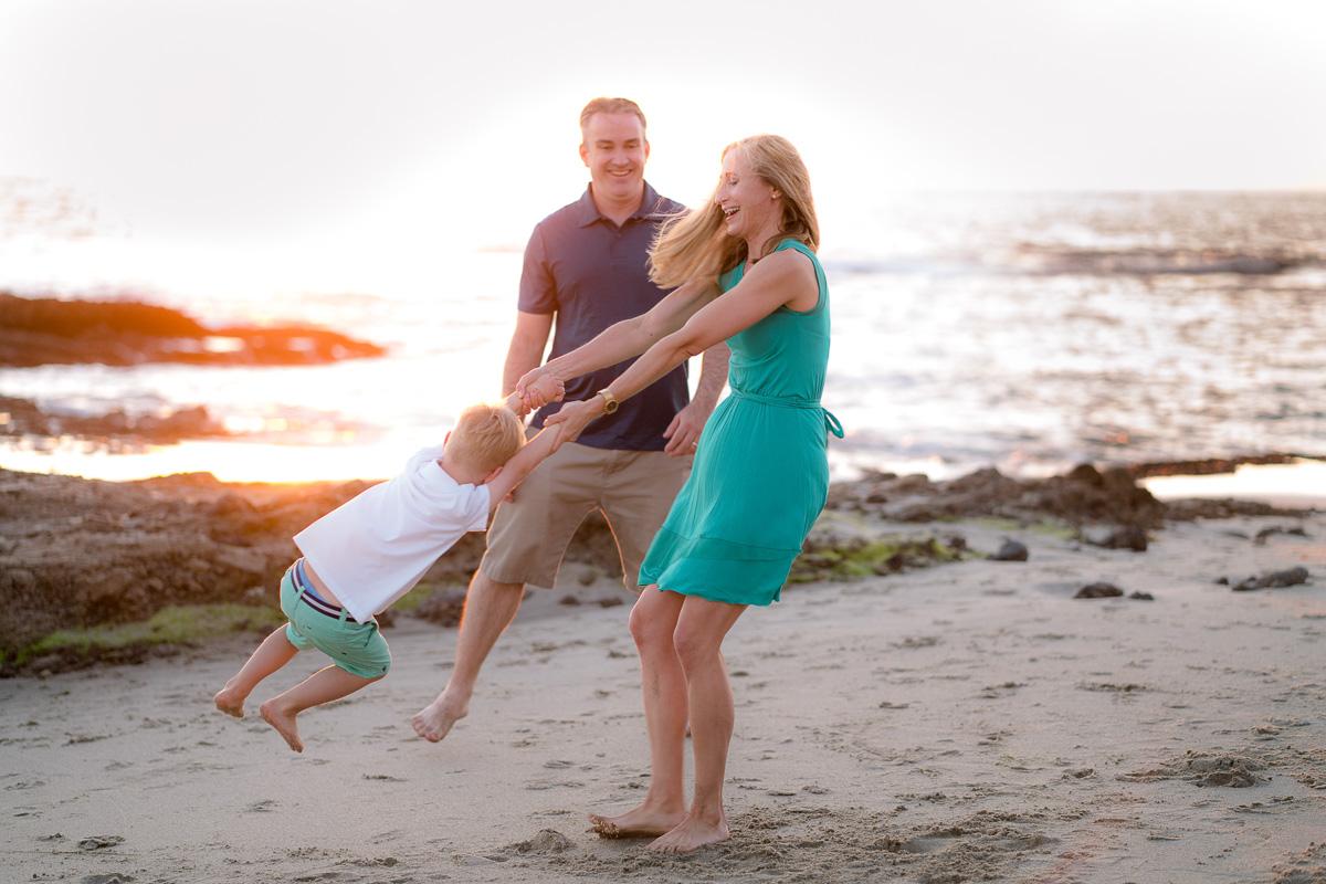 mom and dad swinging kid on beach