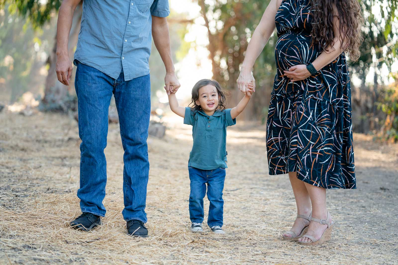 toddler holding pregnant mom and dads hands