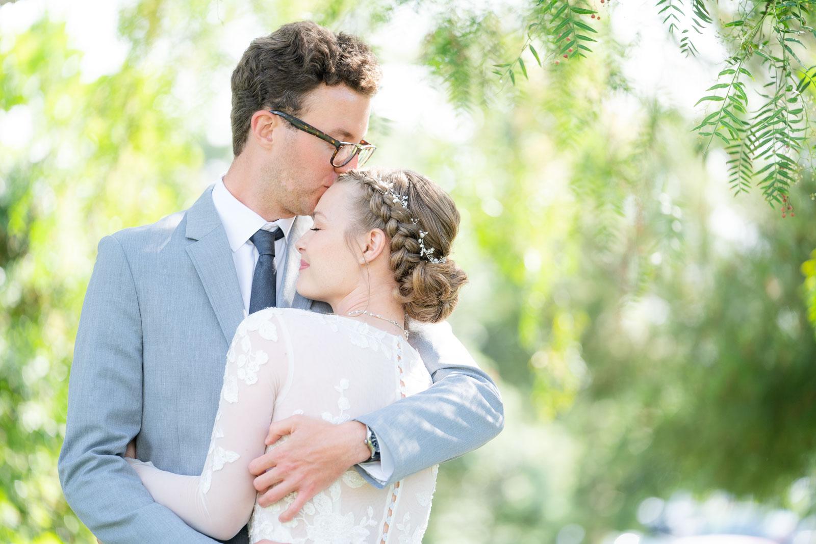 groom kissing his bride on forehead