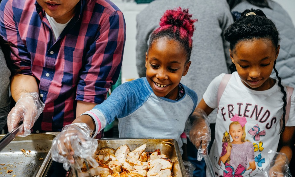 A girl serves food at Open Arms' community dinner