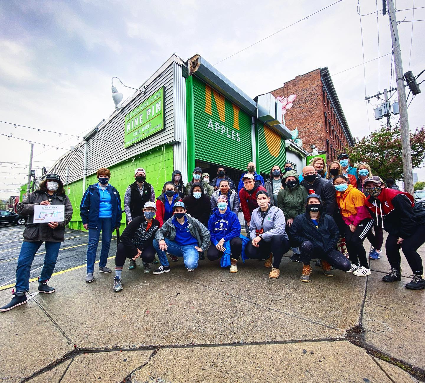 A group of 20 or people posing in front a green warehouse.