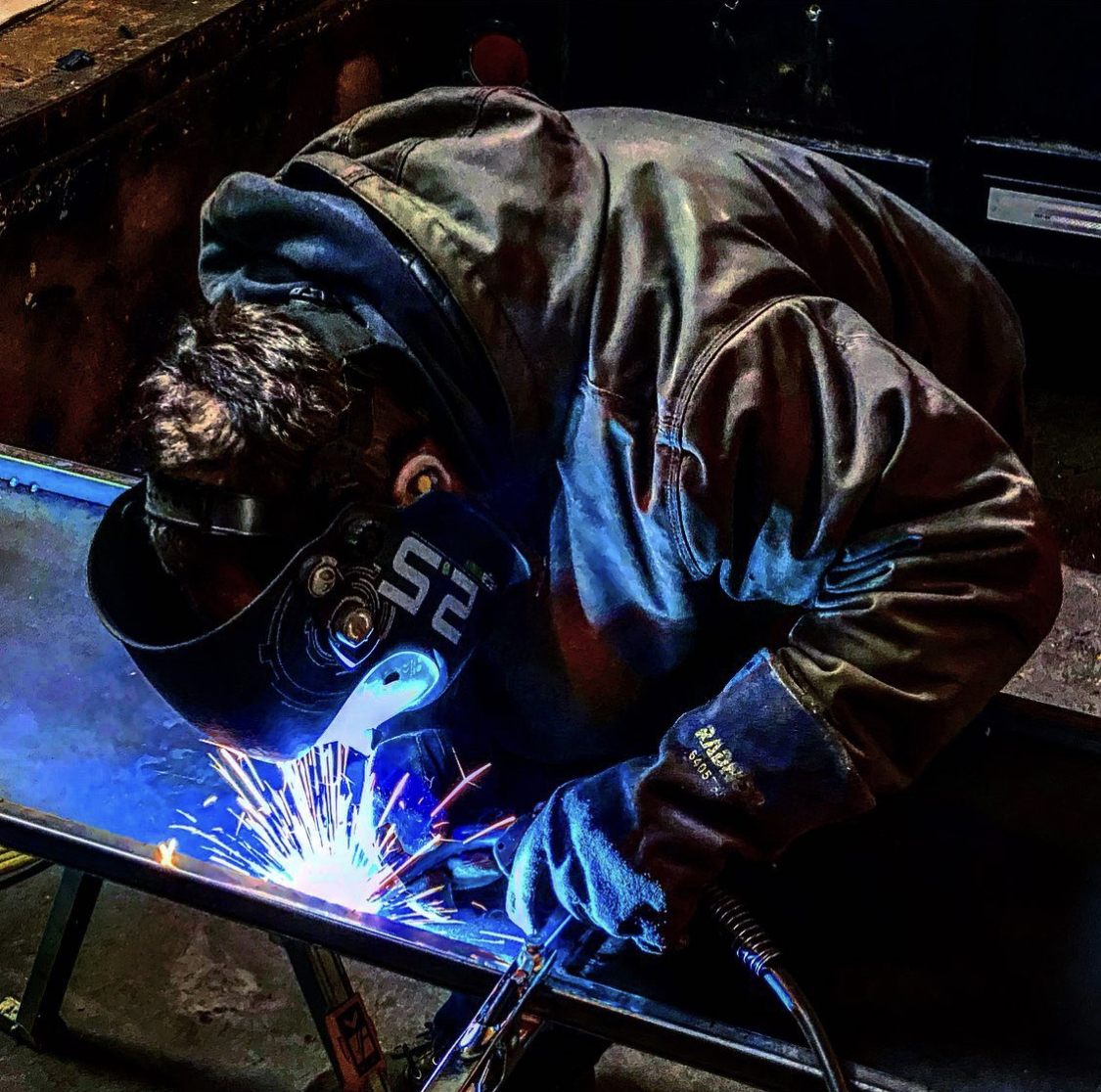 A man welding metal, with sparks flying from his work station