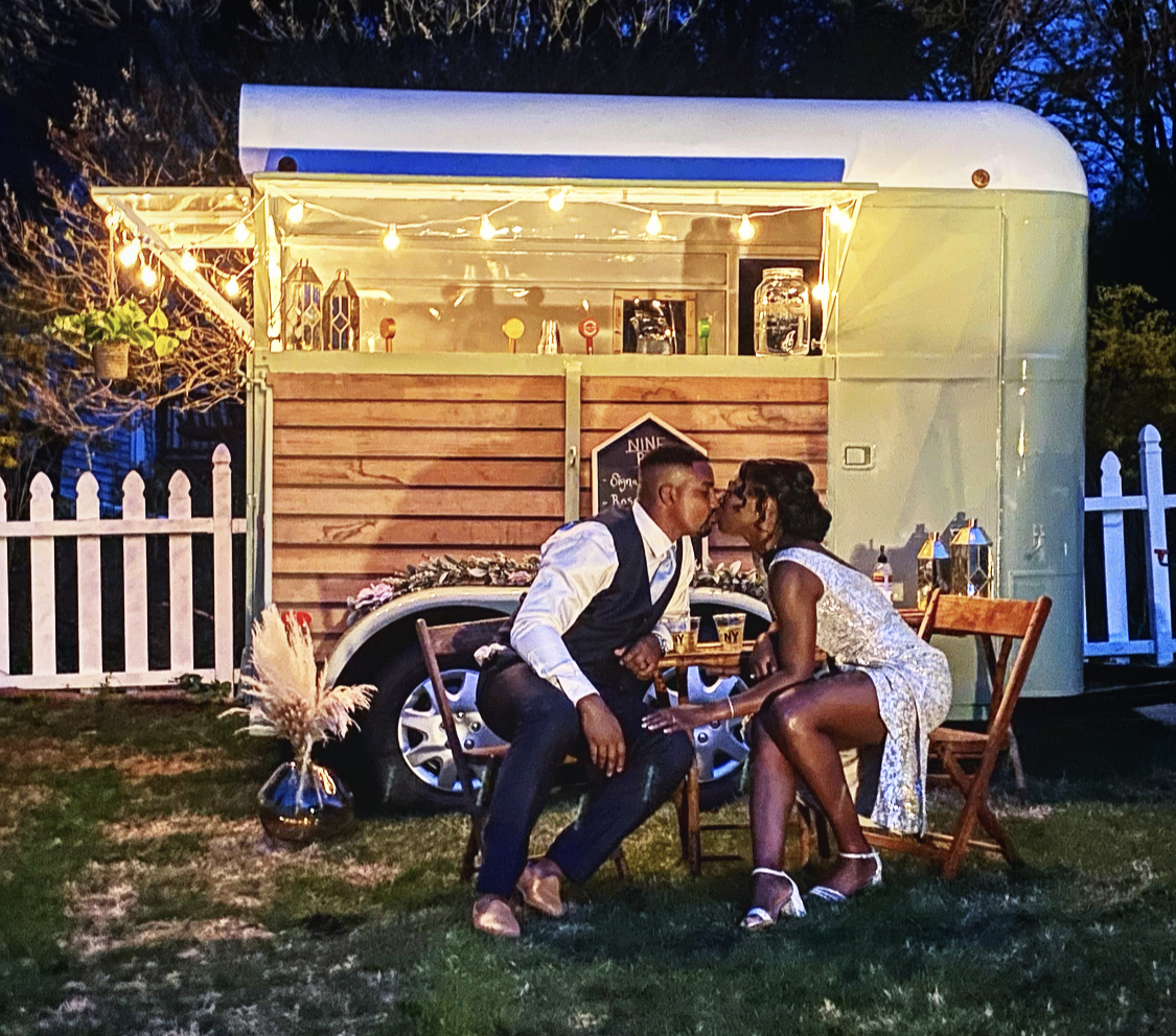 A beautiful bride and groom kissing in front of a mobile wedding bar.