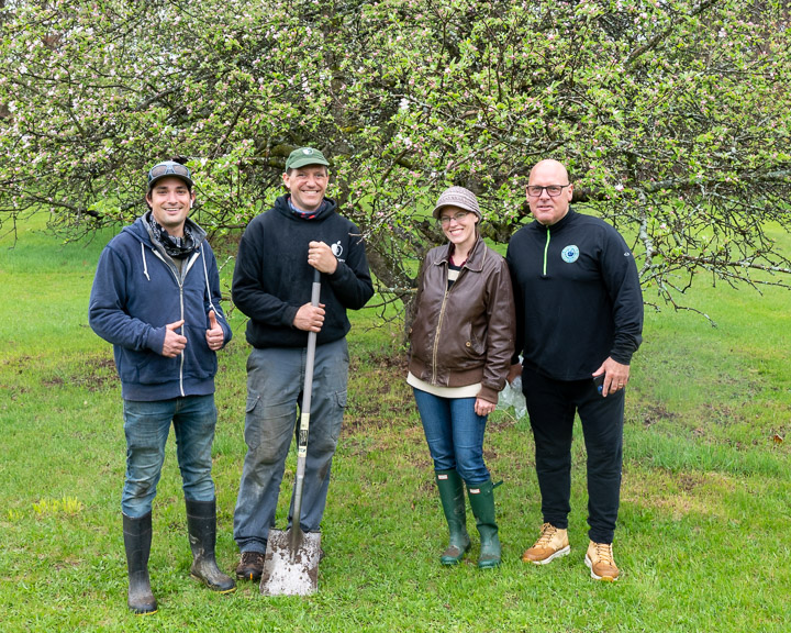 A group of 4 people, 3 men and 1 women, smiling in front of an apple tree