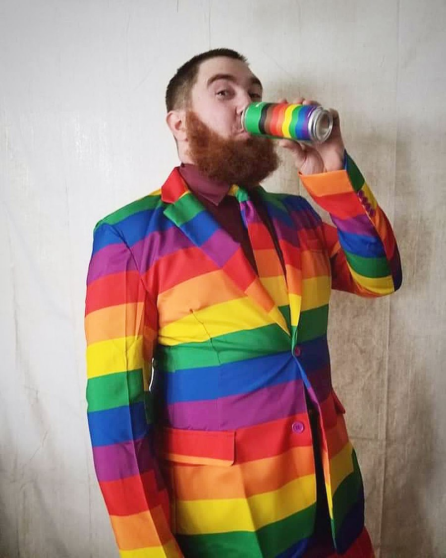Dark haired man with rainbow color suit drinking a rainbow color Nine Pin Pride can