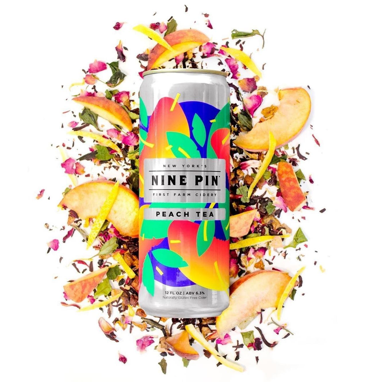 Bright and color full Nine Pin Cider can laying on peach slices and peach tea