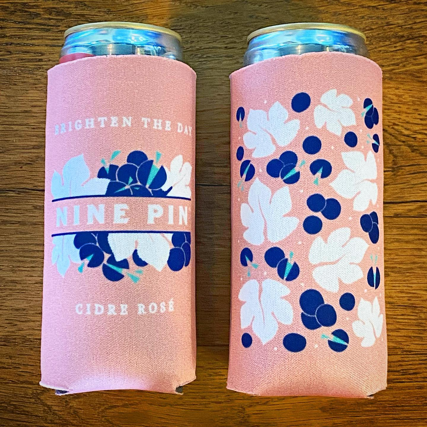 """Two Blue, white and pink Nine Pin Cidre Rosé can koozies. Text reads """"Brighten the Day"""""""