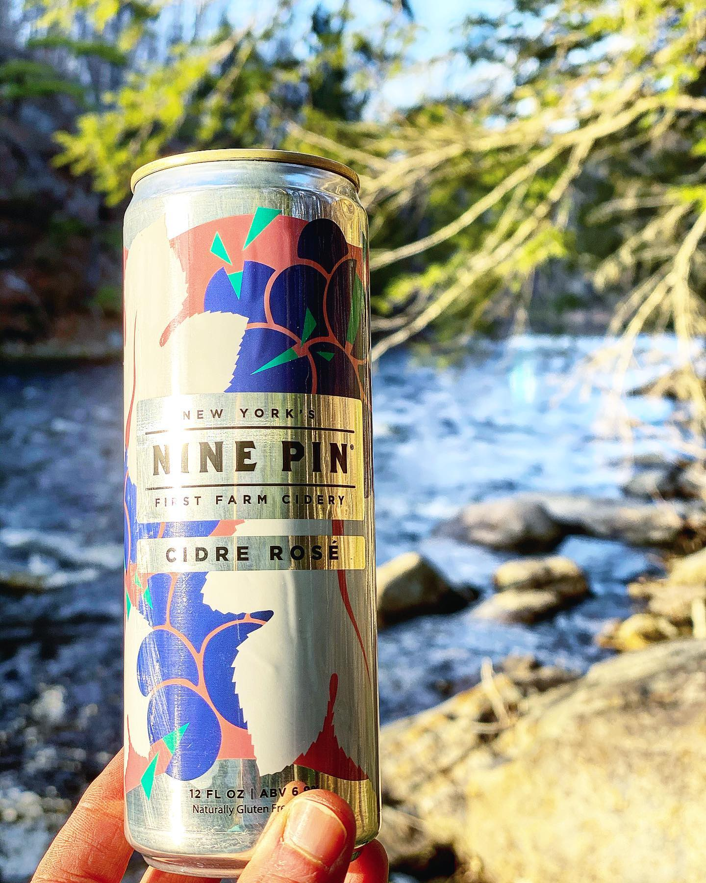 Blue, white and pink Nine Pin Cidre Rosé can in front of a rocky river