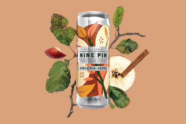 Nine Pin Cider Apple Pie-Secco can on a brown background and apple slices and apple tree branches behind it