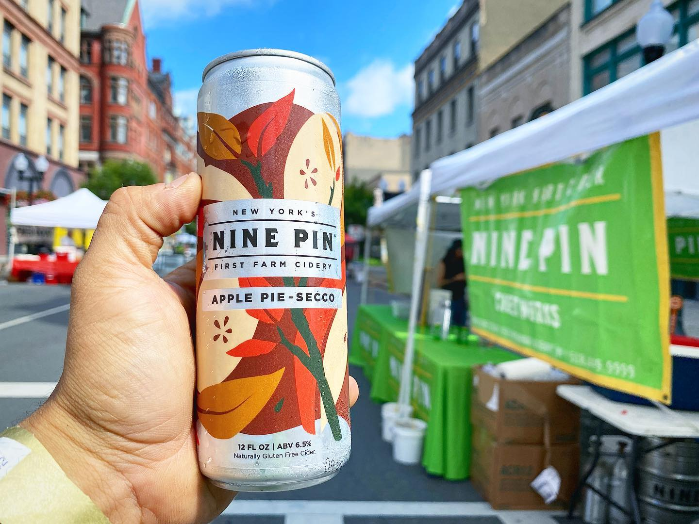 Nine Pin Apple Pie-Secco in front of green Nine Pin Cider sign on Pearl Street in Albany, NY.