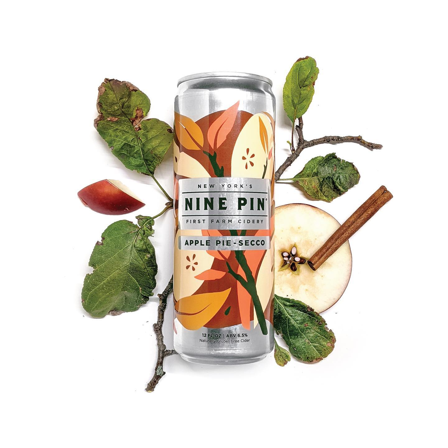 Brown and burgundy Nine Pin Apple Pie-Secco can on top of apple branches and apple slices.