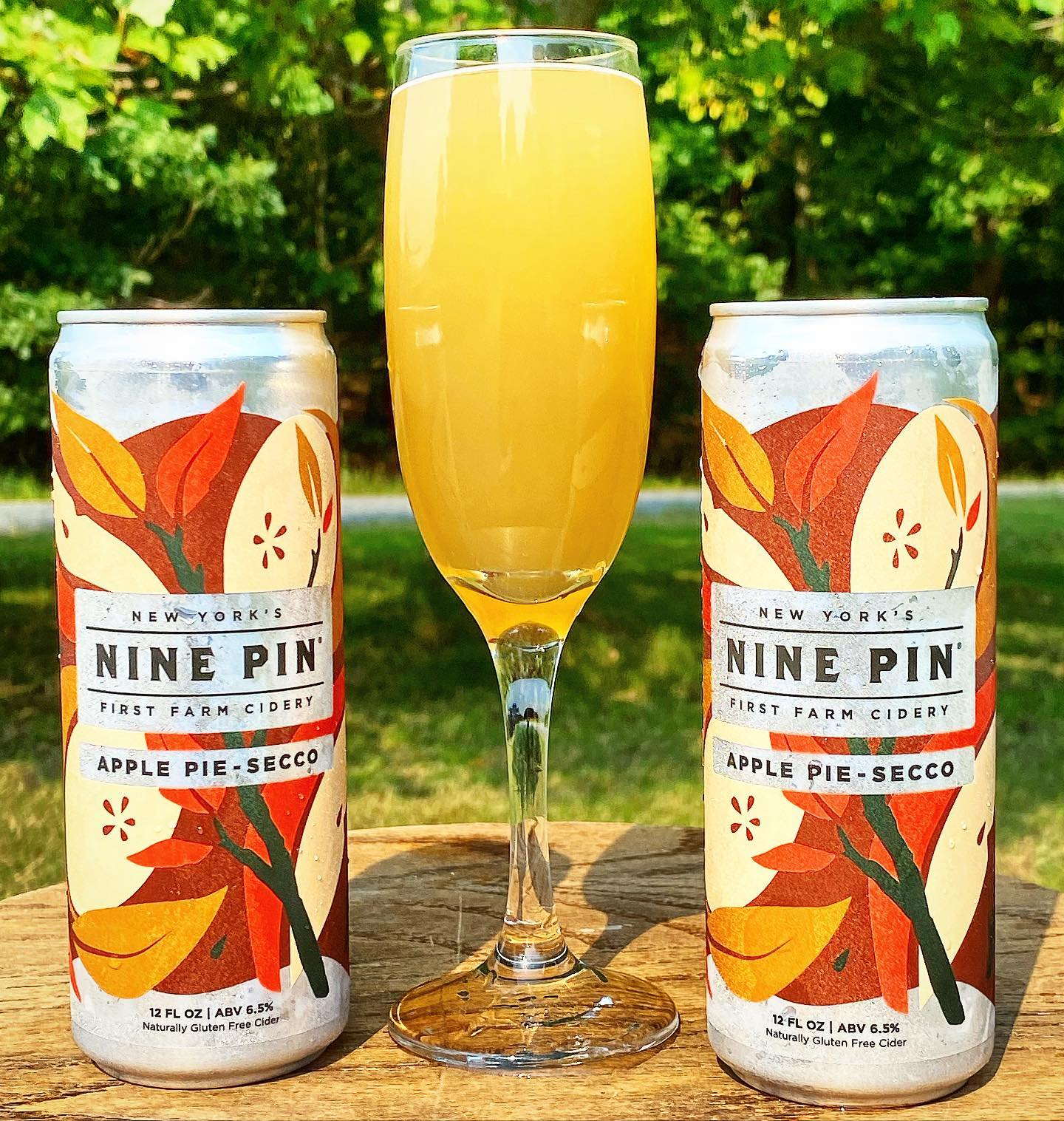 A cider mimosa in between two cans of Nine Pin Apple Pie-Secco